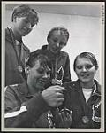 MIKAN 4814149 Elaine Tanner (left, first row) and other members of the Canadian swimming team with their medals at the 1967 Pan Am Games in Winnipeg  1967. [221 KB, 1000 X 1244]