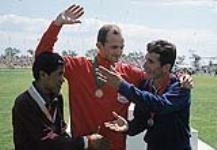 MIKAN 4814190 Andy Boychuk du Canada (au centre), gagnant du marathon, avec le médaillé d¿argent Agustin Calle de la Colombie (à gauche) et le médaillé de bronze Alfredo Peñaloza du Mexique (à droite) sur le podium aux Jeux panaméricains de 1967 à Winnipeg  1967. (Andy Boychuk, gagnant du marathon, avec les autres médaillés aux Jeux panaméricains de 1967) [Andy Boychuk du Canada (au centre), gagnant du marathon, avec le médaillé d¿argent Agustin Calle de la Colombie (à gauche) et le médaillé de bronze Alfredo Peñaloza du Mexique (à droite) sur le podium aux Jeux panaméricains de 1967 à Winnipeg, 1967.]