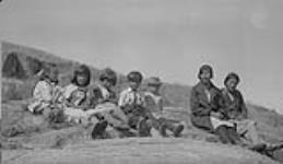 MIKAN 4613675 Groupe d¿enfants métis assis sur un rocher avec deux femmes, Fort Chipewyan (Alberta)  vers 1930-1939. [Groupe d¿enfants métis assis sur un rocher avec deux femmes, Fort Chipewyan (Alberta), vers 1930-1939.]