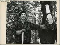 """MIKAN 3197737 Lumberman and """"skidder"""" Edoma Rozon of Mont Clerf, Quebec, poses with pulp hook on his shoulder with his horse, """"George"""". Mar. 1943 [152 KB, 1000 X 756]"""
