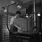 MIKAN 4948775 A parish record book being captured onto microfilm. 1956 [122 KB, 1000 X 1003]