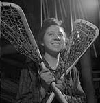 "MIKAN 4949018 Ms. [Elizabeth ""Bessie""] Roundpoint [Cole] poses with lacrosse sticks  1957 [148 KB, 1000 X 1023]"