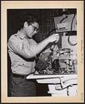 MIKAN 5320424 Gilbert George Oskaboose of Serpent River Band, Sault Ste. Marie Agency is taking an outboard marine mechanics course at the Standard Engineering Institute in Toronto as a student under the Indian Affairs Placement Program. [between 1900-1976] [Gilbert George Oskaboose of Serpent River Band, Sault Ste. Marie Agency is taking an outboard marine mechanics course at the Standard Engineering Institute in Toronto as a student under the Indian Affairs Placement Program., [between 1900-1976]]