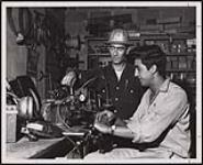 MIKAN 5320430 Melvin Pervais (right) works in the instrumentation division of the sulphuric plant at Culter as a repair and maintenance man. [ca. 1959] [Melvin Pervais (right) works in the instrumentation division of the sulphuric plant at Culter as a repair and maintenance man., [ca. 1959]]