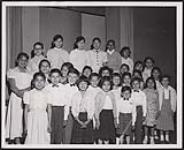 MIKAN 5320408 The children of the Saugeen Indian Village School choir, under the direction of Dolores Enderwick, were highly commended when they sand recently at a concert in the Owen Sound City Hall. [ca. 1957] [The children of the Saugeen Indian Village School choir, under the direction of Dolores Enderwick, were highly commended when they sand recently at a concert in the Owen Sound City Hall., [ca. 1957]]