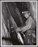 MIKAN 5320390 [First Nations miner drilling in Pickle Crow Gold Mines in Northern Ontario]. Original title: One of the Indian employed as a miner in the Pickle Crow Gold Mines in Northern Ontario. [ca. 1957] [[First Nations miner drilling in Pickle Crow Gold Mines in Northern Ontario]. Original title: One of the Indian employed as a miner in the Pickle Crow Gold Mines in Northern Ontario., [ca. 1957]]