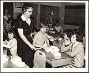 MIKAN 5320335 Integration a success - Mrs. L. C. Anderson checks her students during a lunch-hour break at Ridgetown Public School, 22 miles northeast of Chatham. November 1958 [Integration a success - Mrs. L. C. Anderson checks her students during a lunch-hour break at Ridgetown Public School, 22 miles northeast of Chatham., November 1958]