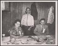 MIKAN 5320331 Fair Officials who guided the successful 1959 Mohawk Fair at the Tyendinaga Indian Reserve near Deseronto, included Mrs. Helen Louis, secretary; John A. Brant, the treasurer (standing), and Clifford Maracle, president, shown here in the fair's office during the show. Fall 1959 [Fair Officials who guided the successful 1959 Mohawk Fair at the Tyendinaga Indian Reserve near Deseronto, included Mrs. Helen Louis, secretary; John A. Brant, the treasurer (standing), and Clifford Maracle, president, shown here in the fair's office during the show., Fall 1959]