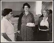 MIKAN 5320334 Cooking prizes at the 1959 Mohawk Fair were won by Mrs. Susan Claus, shown at right, and Mrs. Ruby Brant, middle holding cakes which on them top prizes. Fall 1959 [Cooking prizes at the 1959 Mohawk Fair were won by Mrs. Susan Claus, shown at right, and Mrs. Ruby Brant, middle holding cakes which on them top prizes., Fall 1959]