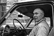 MIKAN 5320297 [Portrait of Councillor Reginald Scero, Kanien¿keha:ka (Mohawk) from Tyendinaga, sitting in the driver's seat of a car, with the door open]. [ca. 1959] [[Portrait of Councillor Reginald Scero, Kanien¿keha:ka (Mohawk) from Tyendinaga, sitting in the driver's seat of a car, with the door open]., [ca. 1959]]