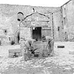 MIKAN 5176159 Filling water cans from 13th Century well at castle at Castel Lagopesole. Cpl. J. Pearson and Pte. J. Milligan, both PPCLI. 1943. [284 KB, 1000 X 1000]