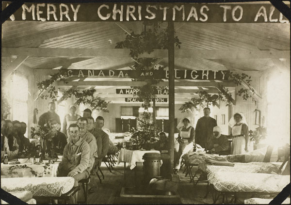 Photograph of three nursing sisters with patients in a Christmas-decorated ward, No. 2 Canadian General Hospital, Le Tréport, France, December 1916
