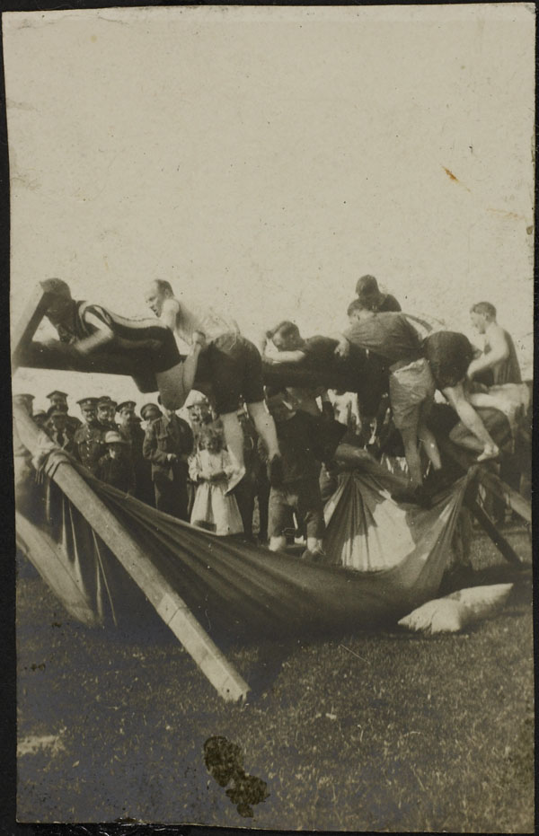 Photograph of a group of men having a pillow fight on a horizontal greased pole, Dominion Day Sports, No. 2 Canadian General Hospital, Le Tréport, France, July 2, 1917