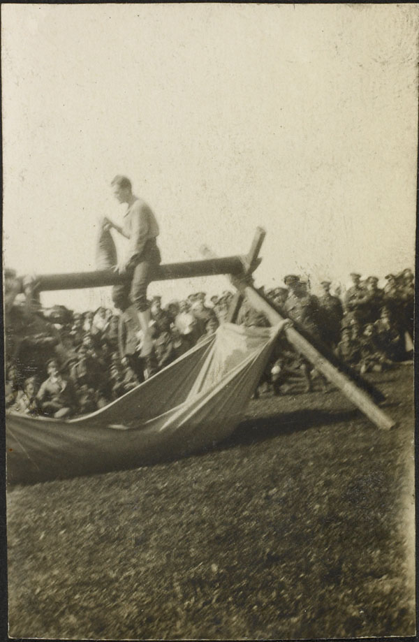 Photograph of one of the contestants having a pillow fight on a horizontal greased pole, Dominion Day Sports, No. 2 Canadian General Hospital, Le Tréport, France, July 2, 1917